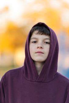 Odkryty przystojny chłopak portret. nastoletnia chłopiec w kapiszonie nad parkowym natury tłem.