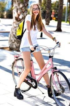 Odkryty słoneczny letni portret radosnej szczęśliwej uśmiechniętej blondynki, krzyczącej śmiejąc się i bawiąc się, jeżdżąc na rowerze retro vintage hipster, ubranie, jasny makijaż, podróże, wakacje lato.
