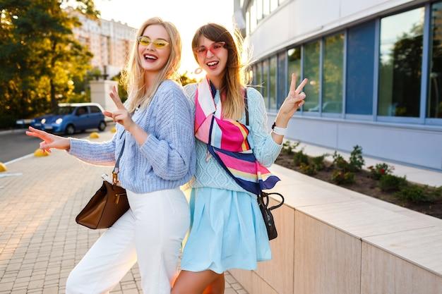 Odkryty słoneczny portret szczęśliwej pary eleganckich dziewczyn, które bawią się razem na ulicy, stylowe stroje vintage, pastelowe swetry i okulary przeciwsłoneczne, pasujące akcesoria, czas z rodziną.