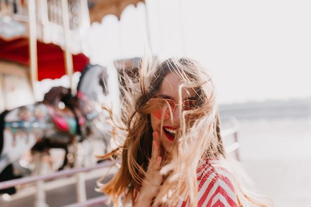 Odkryty strzał błogiej dziewczyny słodkie wyrażające pozytywne emocje. marzycielska młoda kobieta w okularach przeciwsłonecznych z przyjemnością pozuje w parku rozrywki.