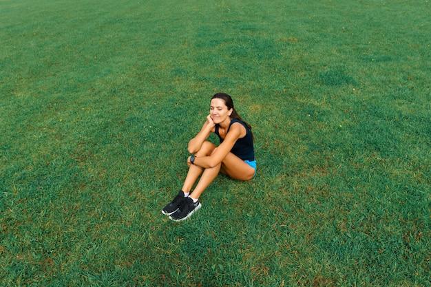 Odkryty strzał lekkoatletka młoda kobieta działa na torze wyścigowym. zawodowa sportsmenka podczas treningu biegowego.