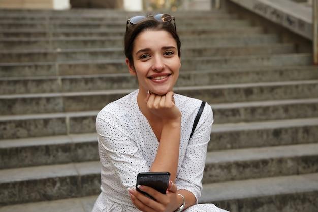 Odkryty strzał młodej atrakcyjnej ciemnowłosej kobiety opierającej brodę na uniesionej dłoni i uśmiechającej się szczerze, siedzącej nad schodami miasta w ciepły wiosenny dzień z telefonem komórkowym