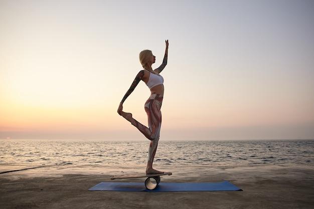 Odkryty strzał młodej sportowej kobiety stojącej na drewnianym biurku z widokiem na morze, noszącej sportowe ubrania, wykonującej ćwiczenia z balanserem na wybrzeżu, trzymając nogę ręką i podnosząc rękę do góry