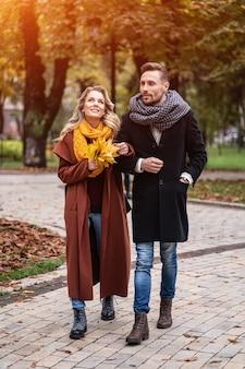 Odkryty strzał młodej uroczej pary zakochanych spaceru ścieżką przez jesienny park