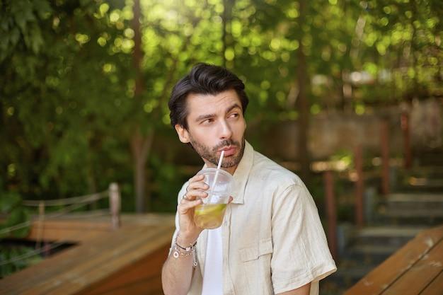 Odkryty strzał młodych ładnych mężczyzn z brodą siedzących na zielonych drzewach na ławce, patrząc na bok i pijąc lemoniadę, ubrany w ubranie