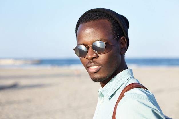 Odkryty strzał modnego młodego człowieka w nakrycia głowy i okularów