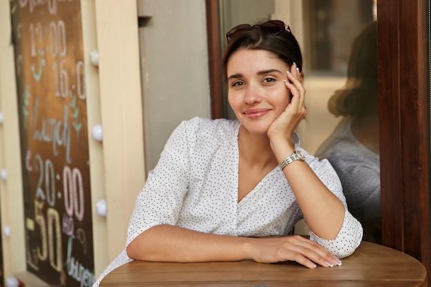 Odkryty strzał pięknej młodej brązowookiej kobiety frunette siedzi przy stole w miejskiej kawiarni, opierając głowę na uniesionej ręce i patrząc z czarującym uśmiechem