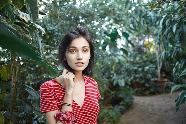 Odkryty strzał pięknej młodej kobiety z włosami bob noszącej czerwoną sukienkę w paski pozuje na rozmytym tle różnych zielonych drzew i krzewów w przestronnej szklarni, ogrodzie lub szkółce roślin