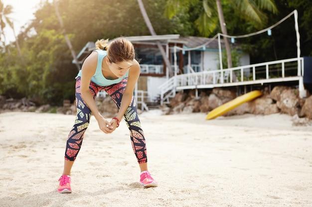 Odkryty strzał wyczerpanej kaukaskiej biegaczki w kolorowych legginsach i różowych trampkach odpoczywającej podczas intensywnego treningu na morzu, stojącej na piasku i pochylającej się, łapiąc oddech