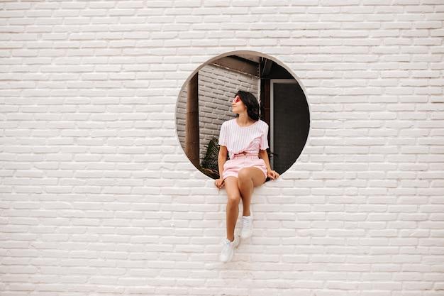 Odkryty strzał zamyślonej kobiety w stroju casual. całkiem opalona młoda kobieta w trampkach siedzi na ceglanej ścianie.