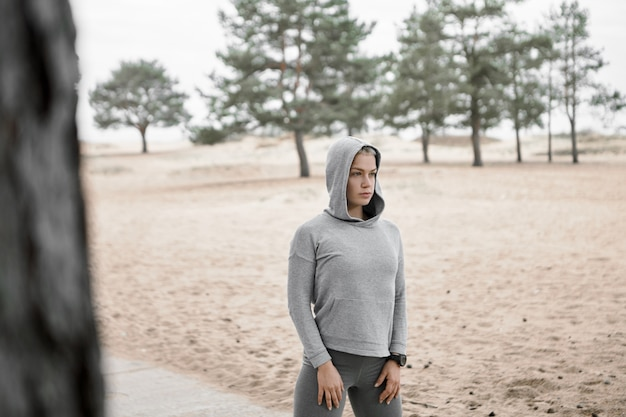 Odkryty wizerunek dopasowanej szczupłej młodej kobiety ubranej w stylową odzież sportową pozuje na zewnątrz z piaszczystą plażą i sosnami w tle, ćwicząc, wykonując poranny trening. selektywna ostrość