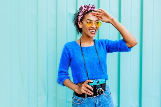 Odkryty wizerunek modnej czarnej kobiety w jasnym wełnianym swetrze i kolorowej opasce na włosach
