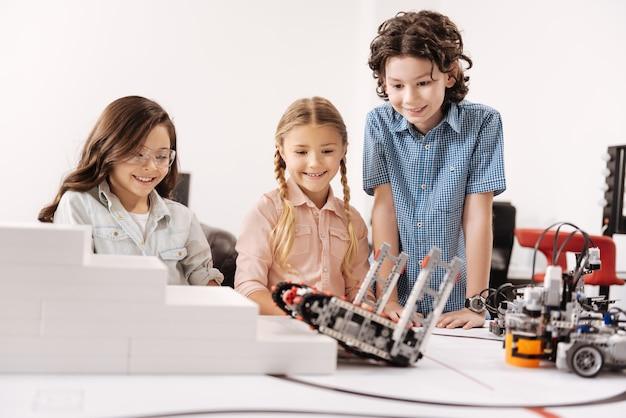 Odkrywanie futurystycznych technologii. rozbawione, radosne dzieciaki siedzące w szkole i testujące cyber robota podczas pracy nad projektem technologicznym