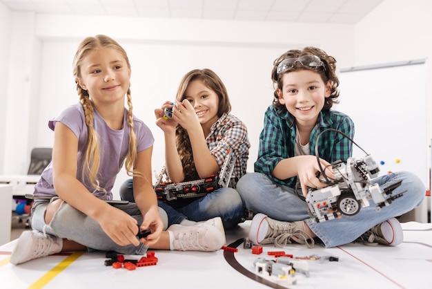 Odkrywanie nowych horyzontów z przyjaciółmi. szczere, żywe, słodkie dzieci siedzące w klasie naukowej i bawiące się gadżetami i urządzeniami, wyrażające radość