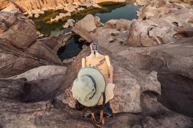 Odkrywca azjatyckiej kobiety siedzącej na skalnym klifie, patrząc na papierową mapę w wielkim kanionie sam phan bok w tajlandii