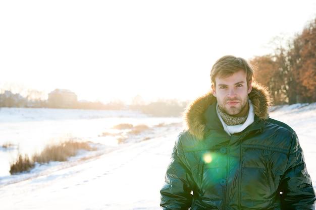 Odkrywca polarny. słoneczny zimowy dzień. zimowa odzież męska. zimowy strój. modny strój hipsterski. kaptur kurtki faceta. mężczyzna ciepłą kurtkę śnieżny charakter tła. odzież odporna na wiatr. zimowe warunki pogodowe.