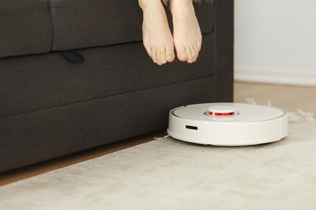Odkurzacz automatyczny do czyszczenia pokoju, podczas gdy kobieta odpoczywa na kanapie. selektywna koncentracja na robotic