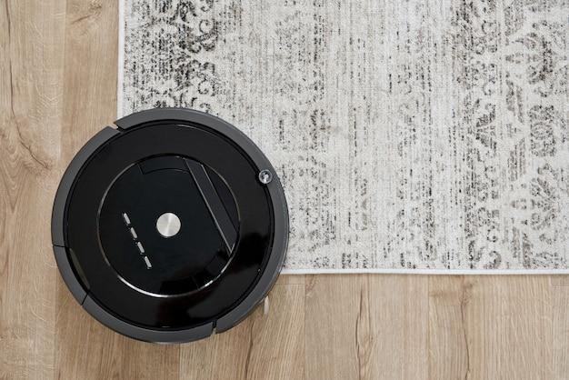 Odkurzacz automatyczny na podłodze w przytulnym nowoczesnym salonie