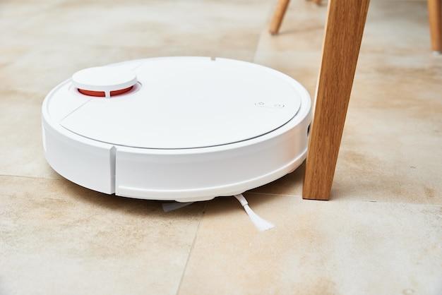 Odkurzacz automatyczny pracujący na podłodze z meblami, przeszkody dla odkurzacza automatycznego. nowoczesne inteligentne gospodarstwo domowe