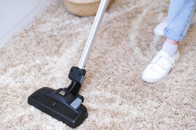 Odkurzacz bezprzewodowy służy do czyszczenia dywanu w pokoju. prace domowe z nowym odkurzaczem ręcznym. koncepcja czyszczenia, pielęgnacji i technologii domu.
