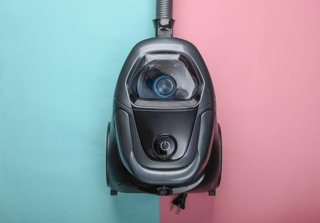 Odkurzacz na różowo-niebieskiej pastelowej powierzchni