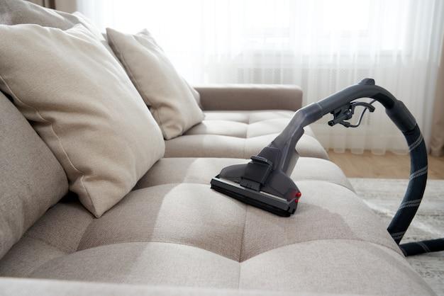 Odkurzacz na sofie w pustym salonie w nowoczesnym mieszkaniu