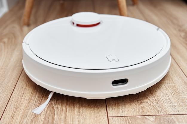Odkurzacz robot pracujący na podłodze laminowanej. technologia domowa z pilotem