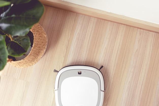 Odkurzacz robot wykonuje automatyczne czyszczenie podłogi.