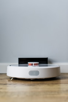 Odkurzacz robota na drewnianej podłodze. widok z boku. inteligentna koncepcja domu. automatyczne czyszczenie.