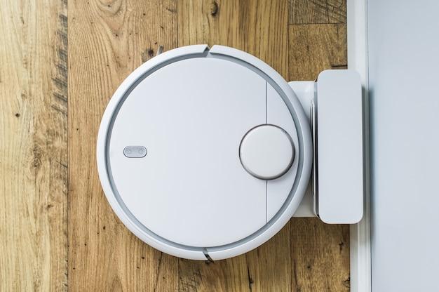 Odkurzacz robota na drewnianej podłodze. widok z góry. inteligentna koncepcja domu. automatyczne czyszczenie