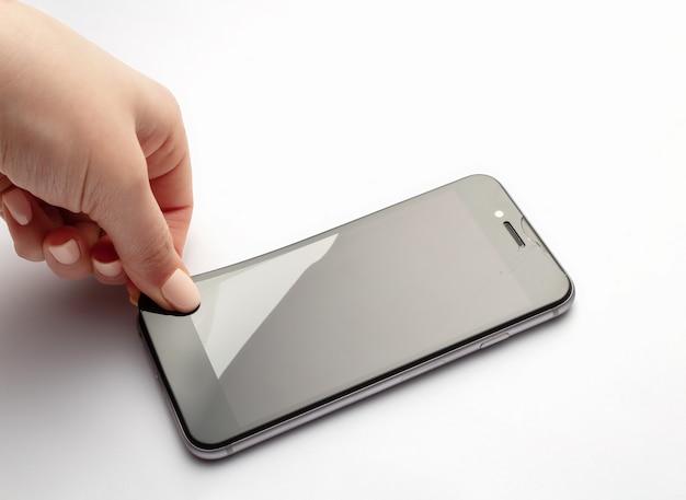 Odłączanie szkła ochronnego od smartfona.