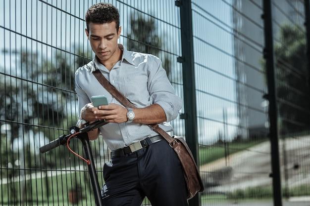 Odległość do pracy. niski kąt przystojnego, miłego faceta, który uruchamia aplikację i opiera się o płot