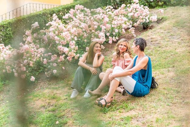 Odległy widok trzech dorosłych kobiet siedzących w parku rozmawia. piękne dojrzałe kobiety bawią się razem w parku.