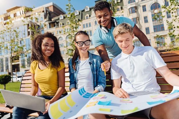 Odłóż to. pozytywni uczniowie, którzy siedzą na ławce, zachowują uśmiech na twarzach i patrzą na pracę nad projektem