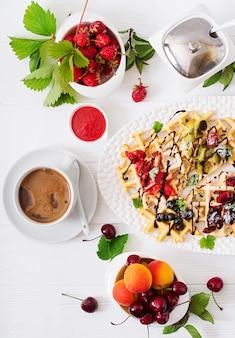 Odmiana belgijskich wafli z jagodami, czekoladą i syropem.