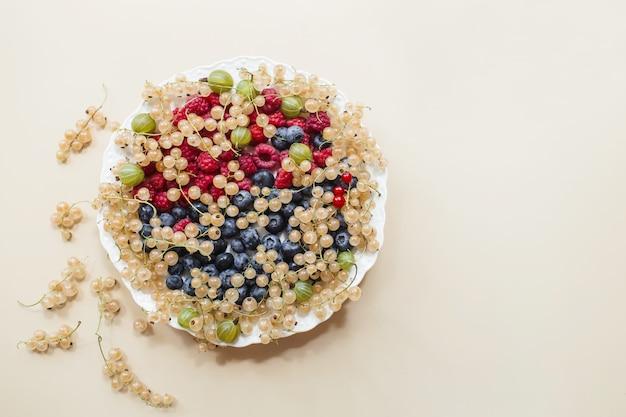 Odmiana jagód świeżych porzeczek biała, jagody, maliny na białym talerzu na beżowym tle. leżał na płasko, widok z góry, miejsce na kopię.