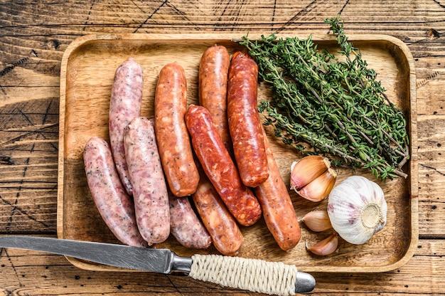 Odmiana kiełbas surowych, mięso wołowe i wieprzowe. drewniane tła. widok z góry.