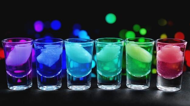 Odmiana mocnych szotów alkoholowych z lodem serwowana na ladzie barowej. rozmycie neonowego tła