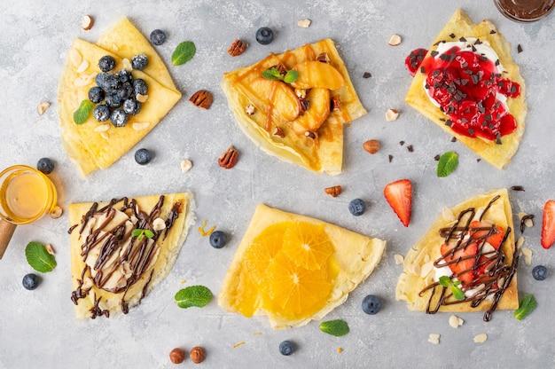Odmiana naleśników lub cienkich naleśników ze świeżymi owocami, jagodami, twarożkiem, miodem, sosem czekoladowym na szarym betonowym tle. widok z góry, miejsce na kopię.