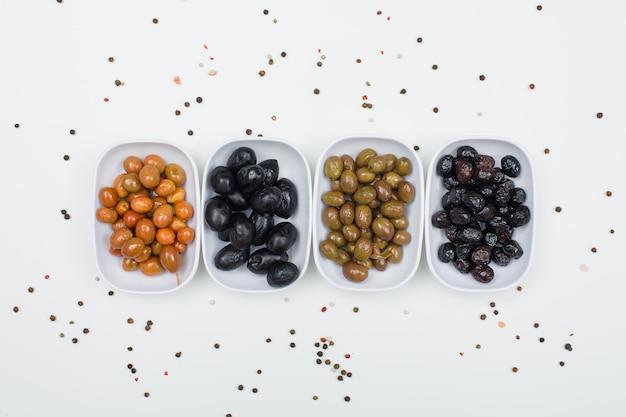 Odmiana oliwek z przyprawami w białe talerze na białym, widok z góry.