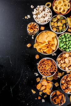 Odmiana różne niezdrowe krakersy z przekąskami, słodki solony popcorn, tortille, orzechy, słomki, bretony