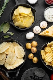 Odmiana różnych chipsów ziemniaczanych, na czarnym tle z kamienia, widok z góry na płasko