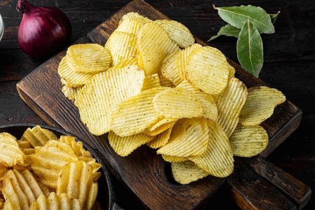 Odmiana różnych chipsów ziemniaczanych, na starym ciemnym drewnianym stole