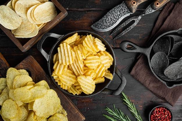Odmiana różnych zestawów chipsów ziemniaczanych, na starym ciemnym drewnianym stole, widok z góry na płasko