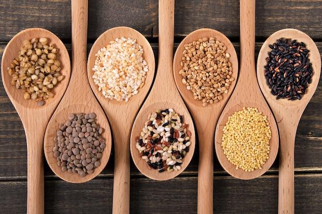 Odmiana ryżu i ziaren w drewnianych łyżkach