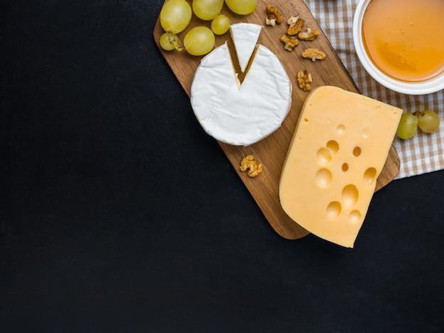 Odmiana sera, orzechów, miodu i winogron na drewnianej desce do krojenia. ser camembert i edam. jedzenie na wino i romantyczne, z widoku z góry.