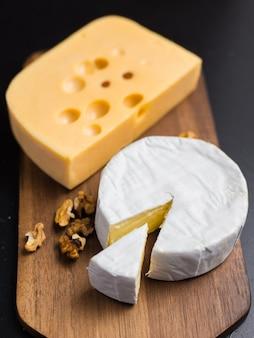 Odmiana sera, orzechów na drewnianej desce do krojenia. ser camembert i ser edamski. jedzenie na wino i romantyczne