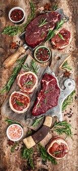 Odmiana steków z surowego mięsa wołowego do grillowania z przyprawami na nożu rzeźniczym. baner, widok z góry na przepis menu. obraz pionowy.