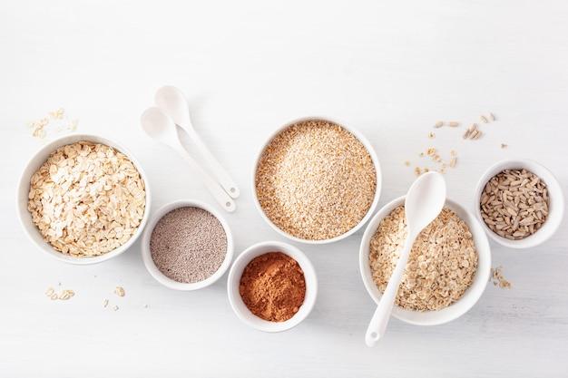 Odmiana surowych płatków i nasion na śniadanie. płatki owsiane i stalowe, jęczmień, chia. zdrowe składniki