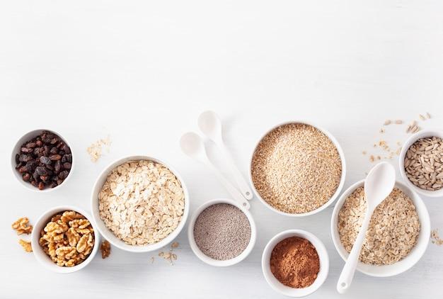 Odmiana surowych płatków śniadaniowych i orzechów. płatki owsiane i stalowe, jęczmień, orzech, chia, rodzynki. zdrowe składniki